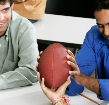 High angle view of three young men looking at a football and talking