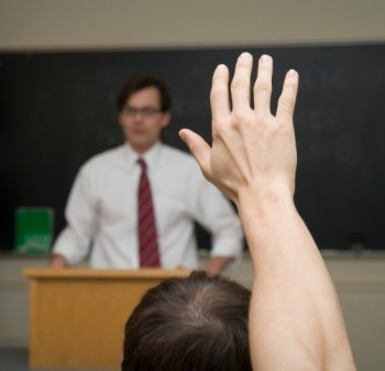 Student with hand raised in lecture room